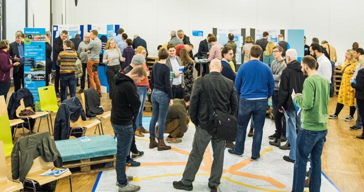 Menschen diskutieren über die Pläne eines hochwertigen ÖPNV-Systems während der Stadtteilforen