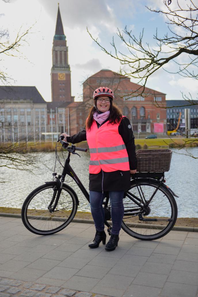 Silke Stolze mit ihrem E-Bike am kleinen Kiel samt Rathaus im Hintergrund