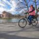 Silke Stolze auf ihrem E-Bike am kleinen Kiel samt Rathaus im Hintergrund