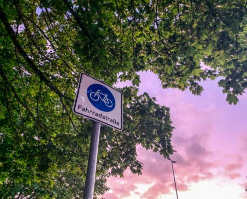 """Ein Schild mit der Aufschrift """"Fahrradstraße"""" zwischen grünen Baumkronen und Abendrot."""