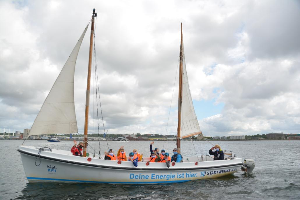 Ein Segelkutter der Stadtwerke Kiel mit mehreren Kinder an Board.